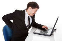 Businessman with lower back ache. From sitting with a bad posture in his office chair working on his laptop massaging his back with his hand Royalty Free Stock Photo
