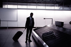 Businessman with luggage at the airport, at conveyor belt Royalty Free Stock Photography