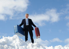 Businessman, Luggage and Snow. A businessman standing outside on a hill of white snow holding 2 suitcases against a bright blue sky with clouds stock photos