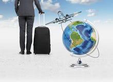 Businessman with luggage. Standing near globe Stock Photos