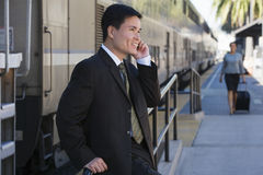 Businessman, with luggage, standing beside stationary train on railway platform, using mobile phone, side view Stock Images