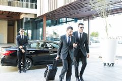 Businessman With Luggage Walking By Bodyguard. Secret service agents giving protection to famous person and his luxury car outside office stock images