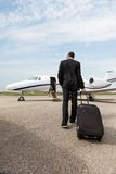 Businessman With Luggage Walking Towards Private. Full length rear view of businessman with luggage walking towards private jet Stock Image