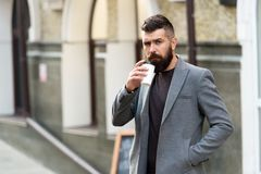 Businessman lumbersexual appearance enjoy coffee break out of business center. Relax and recharge. Man bearded hipster. Drinking coffee paper cup. One more sip stock photography