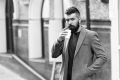 Businessman lumbersexual appearance enjoy coffee break out of business center. Relax and recharge. Man bearded hipster royalty free stock images