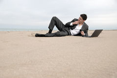 Businessman lying on beach Stock Photos
