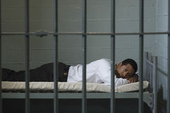 Businessman Lying On Bed In Prison Cell Stock Image
