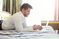 Businessman lying on bed and using laptop. Arabic businessman lying on bed in hotel and using laptop. Smiling man working in hotel room and typing on computer royalty free stock photo