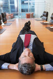 Businessman Lying On Conference Table Stock Photo