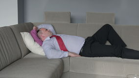 Businessman lying on a couch in living room and having a headache stock footage