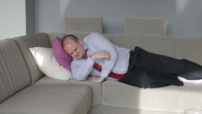Businessman lying on couch in living room and trying to sleep stock video