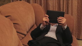 Businessman lying on couch and reading tablet. stock footage