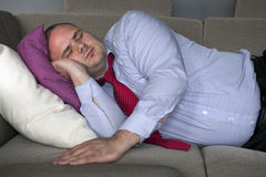 Businessman lying on couch and sleeps Royalty Free Stock Image