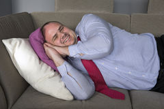 Businessman lying on couch and smiles Stock Photo