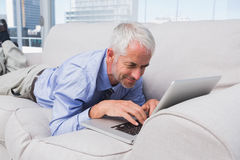 Businessman lying on couch using laptop Stock Photography