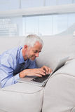 Businessman lying on couch using laptop and smiling Royalty Free Stock Images