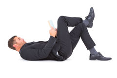 Businessman lying on the floor reading book Stock Photo
