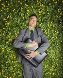 Businessman Lying in Flower Patch. Young businessman with briefcase relaxing in a flower patch smiling with contentment royalty free stock photo