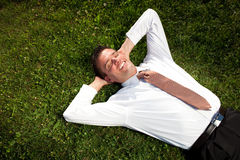 Businessman lying in the grass Stock Image