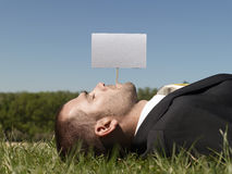 Businessman Lying On Grass With Blank Sign Royalty Free Stock Photography