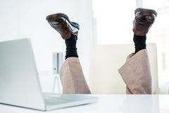 Businessman lying on the ground with feet up Stock Image