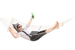 Businessman lying in a hammock and working on a laptop Royalty Free Stock Image