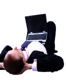 Businessman lying on his back. Laptop on his lap, dreaming about ideas and vision of future business. Isolated on white with copyspace Royalty Free Stock Photos