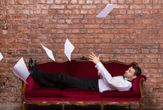Businessman lying on a settee with flying papers. Conceptual image of an elegant businessman lying relaxing on a settee against a brick wall with flying Royalty Free Stock Images