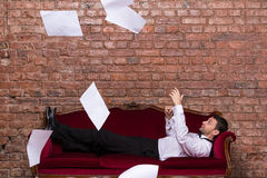 Businessman lying on a settee with flying papers. Conceptual image of an elegant businessman lying relaxing on a settee against a brick wall with flying Royalty Free Stock Photos