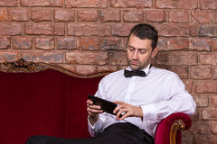 Businessman lying on a settee and reading tablet Stock Photos