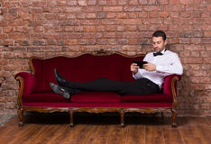 Businessman lying on a settee and reading tablet Royalty Free Stock Photo
