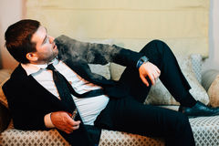 Businessman lying and smokes an electronic cigarette Royalty Free Stock Images