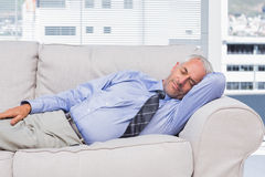 Businessman lying on sofa asleep. In the office Stock Photos