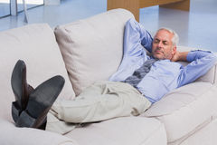 Businessman lying on sofa with his feet up Royalty Free Stock Photos