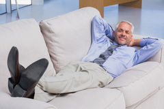 Businessman lying on sofa with his feet up smiling at camera Stock Photos