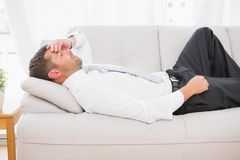 A businessman lying on the sofa at home Royalty Free Stock Images
