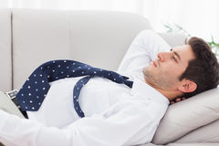 Businessman lying on sofa Royalty Free Stock Images