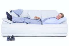 Businessman lying on sofa using his laptop smiling at camera Royalty Free Stock Photography