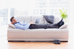 Businessman lying on sofa using his laptop smiling at camera Stock Image