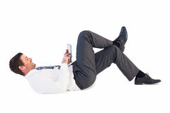 Businessman lying and using tablet Stock Images