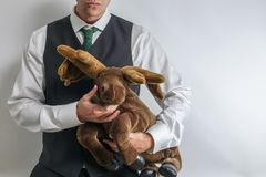 Businessman / mafia boss in suit vest holding a stuffed moose / elk. stock photos