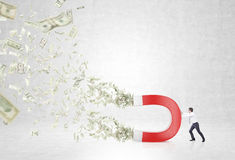 Businessman with magnet. Pulling dollars. Concrete background. Concept of attracting money Royalty Free Stock Image