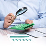 The businessman and magnifier. Businessman working in the office. The magnifier Royalty Free Stock Image