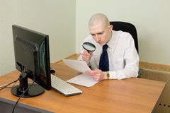 Businessman with a magnifier on a workplace Royalty Free Stock Photo