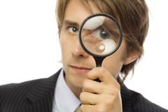 Businessman magnifies. Businessman in a suit looks through a magnifying glass Royalty Free Stock Image