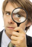 Businessman magnifies. Businessman in a suit looks through a magnifying glass Royalty Free Stock Photography