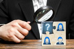 Businessman with a magnifying glass examines the missing part of the puzzle team. Search, recruitment staff, hiring leader. Creating an effective business team stock photography