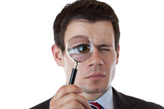 Businessman with magnifying glass at eye Stock Images
