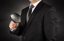 Businessman with magnifying glass Stock Image