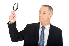 Businessman with a magnifying glass Royalty Free Stock Photo